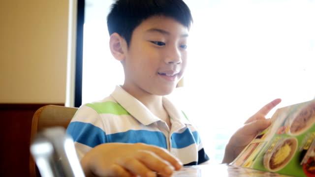lycklig asiatisk söt pojke läsning meny bok och punkt. - empty plate bildbanksvideor och videomaterial från bakom kulisserna