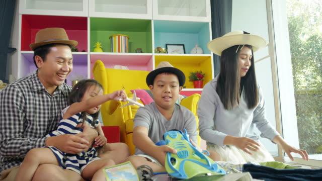 幸せなアジアの家族は、衣類やアクセサリーを梱包をお楽しみください - 楽しい 洗濯点の映像素材/bロール