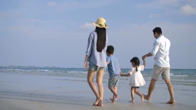 ハッピーアジアの家族が楽しんで、夏休みにビーチを歩いています。スローモーション。家族、休日、旅行のコンセプト。 - 母娘 笑顔 日本人点の映像素材/bロール