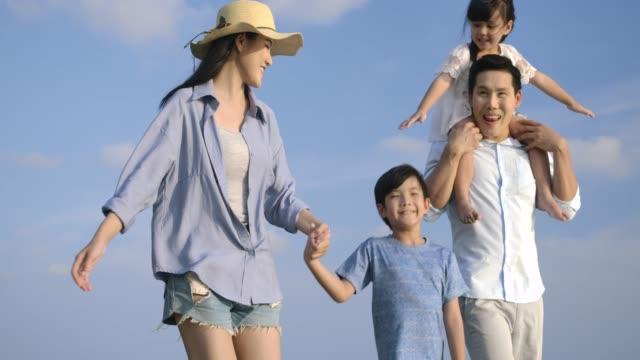 ハッピーアジアの家族が楽しんで、夏休みにビーチを歩いています。スローモーション。家族、休日、旅行のコンセプト。 - 家族 日本人点の映像素材/bロール