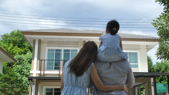 Happy Asian family. Father, mother and daughter near new home. Real estate background.