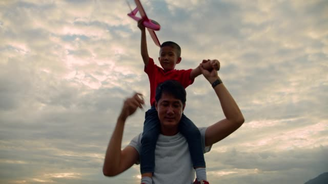 Happy asian family father mother and daughter playing at the natural park when sunset.4k dci slow motion footage. Happy asian family father mother and daughter playing at the natural park when sunset.4k dci slow motion footage.Holding hand walking.playing plane.holding ballon. picnic stock videos & royalty-free footage