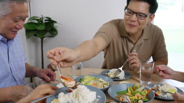 vídeos de stock e filmes b-roll de happy asian family having thai food for dinner together at home - cultura tailandesa