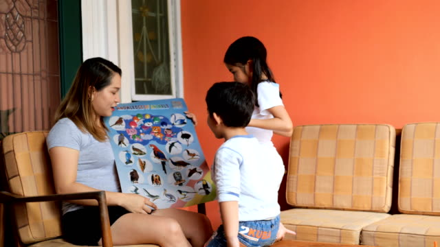 Happy asian family learning new words by boards book.