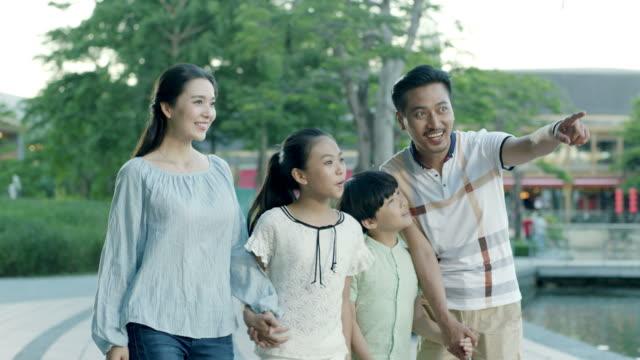 lycklig asiatisk familj 4 pekar & gående mot kameran i slow motion - kinesiskt ursprung bildbanksvideor och videomaterial från bakom kulisserna