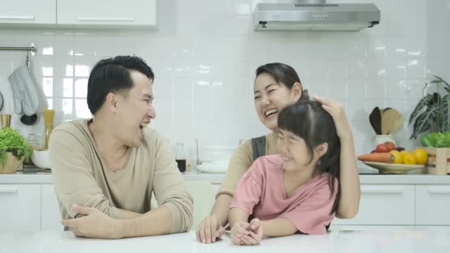 母、父と娘が台所に座って、カメラの前で笑顔の幸せなアジア家族。肖像画を撮影します。屋内で - 母娘 笑顔 日本人点の映像素材/bロール