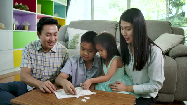 Happy asian family play jigsaw puzzle game together in a living room at home. Happy asian family play jigsaw puzzle game together in a living room at home. playroom stock videos & royalty-free footage