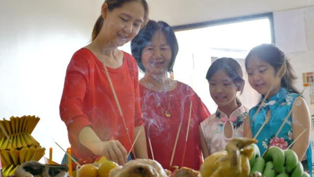 快樂的亞洲家庭在中國新年慶祝活動中祈求繁榮 - chinese new year 個影片檔及 b 捲影像