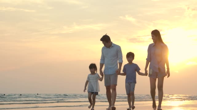 Happy asian family walking down the beach at sunset on summer vacation. Slow motion. Family, Holiday and Travel concept.
