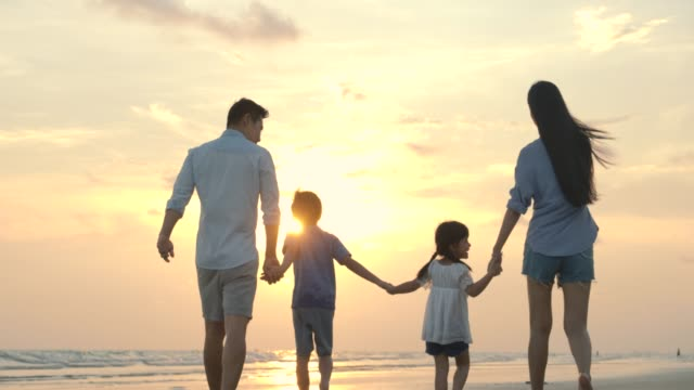 夏休みに夕暮れ時にビーチを歩いて幸せなアジアの家族。スローモーション。家族、休日、旅行のコンセプト。 - 家族 日本人点の映像素材/bロール