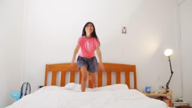 glad asiatisk tjej och sängkläder säng med vitt lakan och täcke med sin bror, livsstil koncept. - duntäcke bildbanksvideor och videomaterial från bakom kulisserna