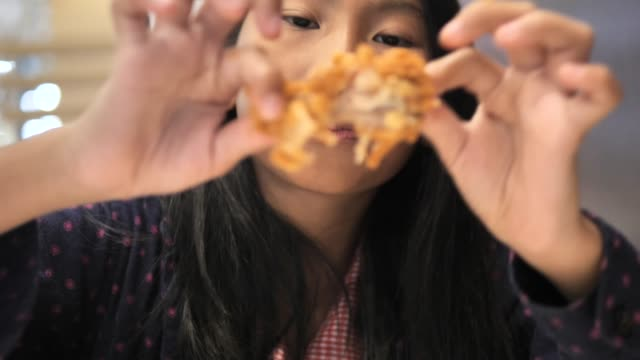 happy asian girl eating spicy fried chicken wing with family at restaurant. - крыло животного стоковые видео и кадры b-roll