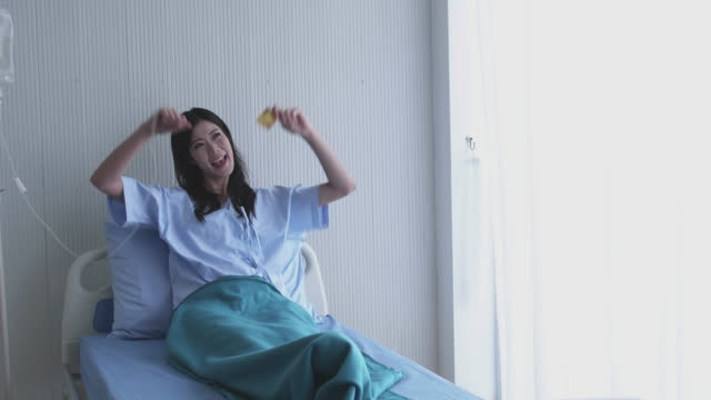 Happy Asian girl on the bed hospital patients. Smiling and Show a credit card. concept payment medical treatment. Dolly shot slide