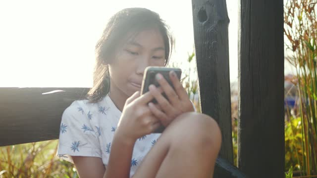 Happy Asian girl sitting on the wooden chair and using smartphone with sunlights background, technology concept.