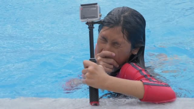 Happy Asian girl swimming at pool and using small sport camera.