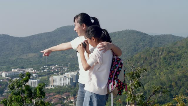 Happy Asian girl using binoculars at the top view of mountain standing with her mother with nature background, lifestyle concept.