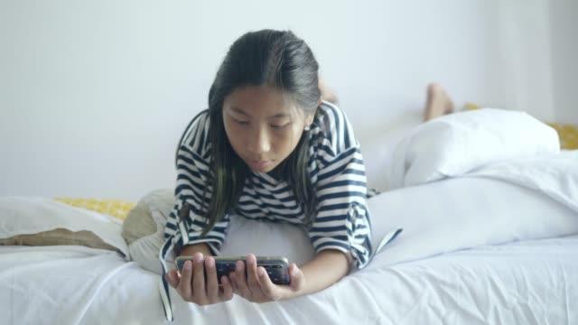 glad asiatisk tjej som använder smartphone och ligger på sängen hemma, livsstilskoncept. - duntäcke bildbanksvideor och videomaterial från bakom kulisserna