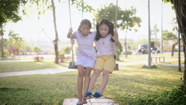 Happy Asian girls playing swing together, slow motion.