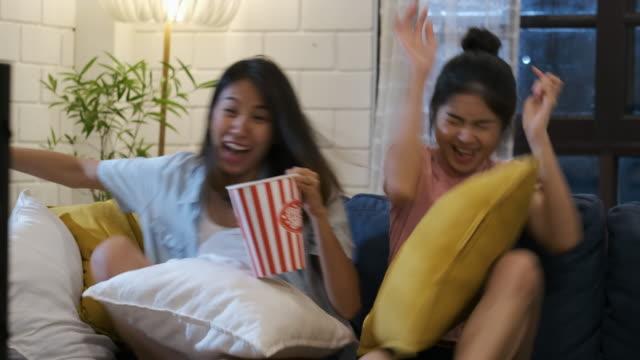vídeos de stock, filmes e b-roll de pares asiáticos felizes da lésbica que prestam atenção ao filme assustador na televisão junto e saltam no sofá no tempo da noite em casa com chill ing emoção. vida da amizade da mulher - horror