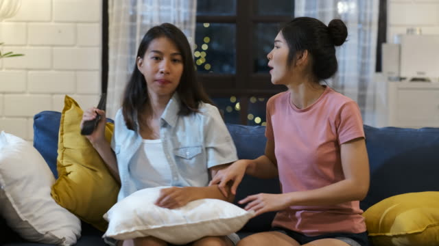 stockvideo's en b-roll-footage met gelukkig aziatische lesbische paar kijken televisie samen en fun vechten voor grab afstandsbediening op de bank in de nacht thuis met chill-out emotie. vrouw vriendschap lifestyle - couple fighting home