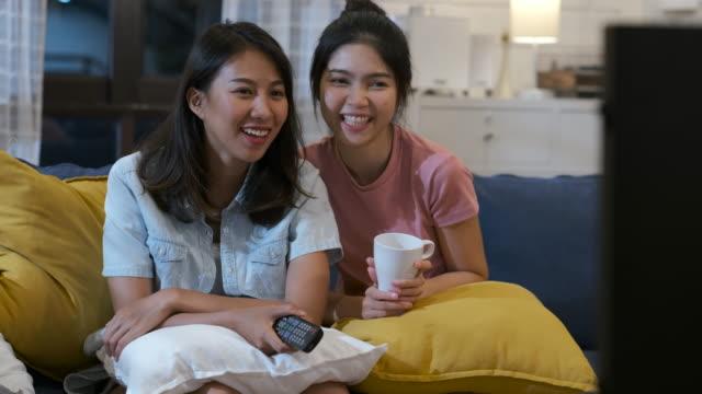 vídeos y material grabado en eventos de stock de feliz pareja lesbiana asiática viendo la televisión juntos en el sofá en la noche en casa con chill ing emotion.mujer amistad lifestyle.panning - family watching tv