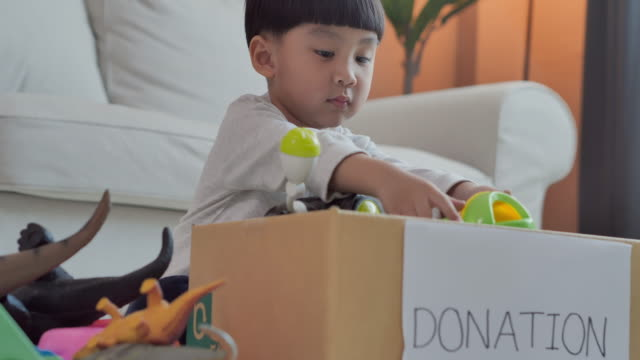 Happy asian little boy age 4 year old of packing to toys into donate box at home.Teaching/learning about Donation Concept