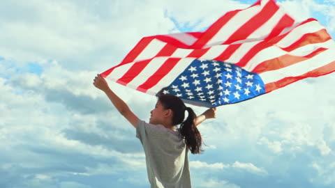 vídeos y material grabado en eventos de stock de feliz niña asiática con bandera americana estados unidos celebrar el 4 de julio - cultura estadounidense