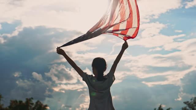 アメリカ国旗 usa とハッピーアジアの少女は、7月4日に祝う - アメリカ文化点の映像素材/bロール