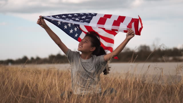 Happy asian little girl with American flag USA celebrate 4th of July Happy asian little girl with American flag USA celebrate 4th of July family 4th of july stock videos & royalty-free footage