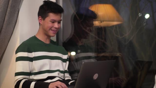 vidéos et rushes de adolescent asiatique heureux s'asseyant sur le rebord de fenêtre et utilisant l'ordinateur portatif. étudiant d'université bel tapant sur le clavier et souriant. internet, les médias sociaux, les technologies modernes. - 18 19 ans