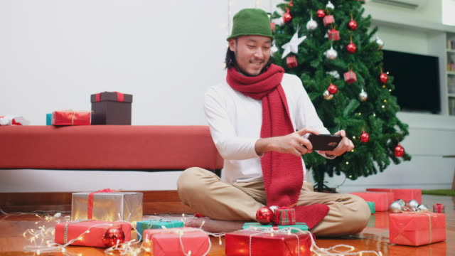 Happy asian man using phone to make video conference showing Christmas gift box, Asia male blogger, vlog recording Christmas present by smart phone