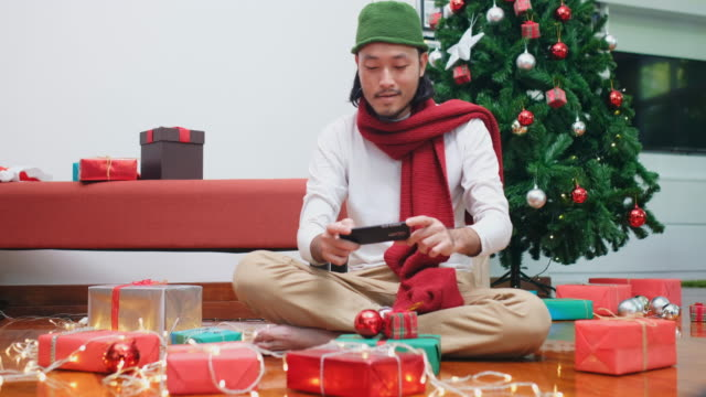 Happy asian man using phone to take picture Christmas gift box, Asia male blogger photographing Christmas present by smart phone