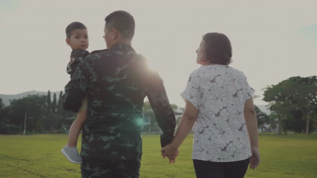 Happy asian military family in garden Exited returning soldier man meeting his wife and son at field in sunset. Thailand. veteran stock videos & royalty-free footage
