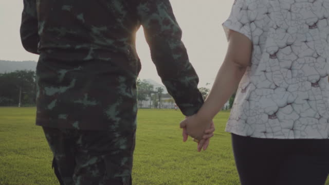 Happy asian military family in garden Exited returning soldier man meeting his wife and son at field in sunset. Thailand. homecoming stock videos & royalty-free footage