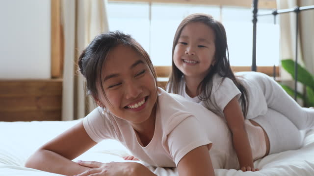 happy asian mom and daughter looking at camera in bed - two students together asian video stock e b–roll