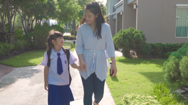 happy asian mother and daughter primary school student walking to school in the morning school routine for day in the life getting ready for school. - two students together asian video stock e b–roll