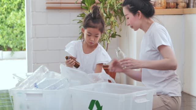 Happy asian mother teaching little girl daughter about sustainability how to recycle household waste at home,Teaching/learning about reusable products and zero waste.Family, Education,Recycling in Daily Life video