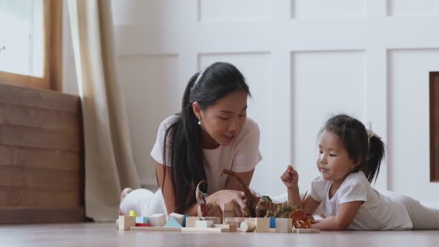 행복한 아시아 엄마 과 아이 딸 재생 공룡 에 바닥 - 유아 스톡 비디오 및 b-롤 화면