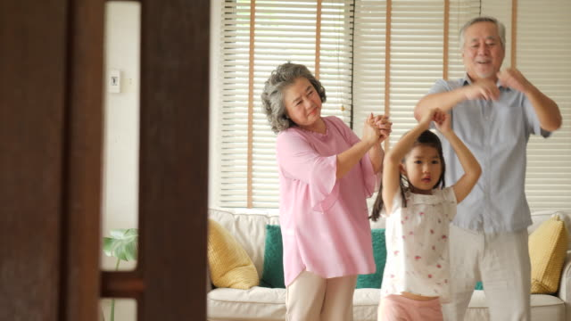 vídeos de stock e filmes b-roll de happy asian senior couple dancing together with their granddaughters at home. senior lifestyle family concept. - etnia asiática
