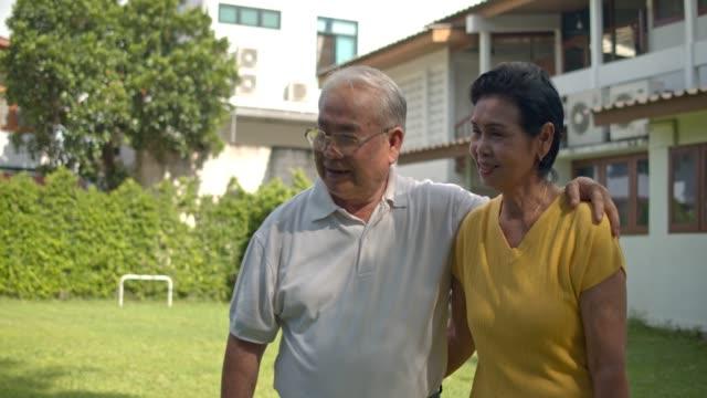 happy Asian senior couple embracing with love in garden,holding hands and walk aroud garden.Senior couple concept.