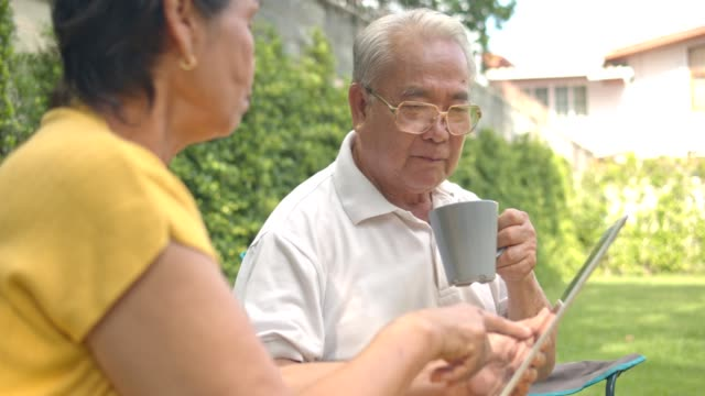 happy Asian senior couple sitting and drinking tea or coffee in the morning at garden home . Having conversation and using tablet ,walking in garden.Senior couple concept.