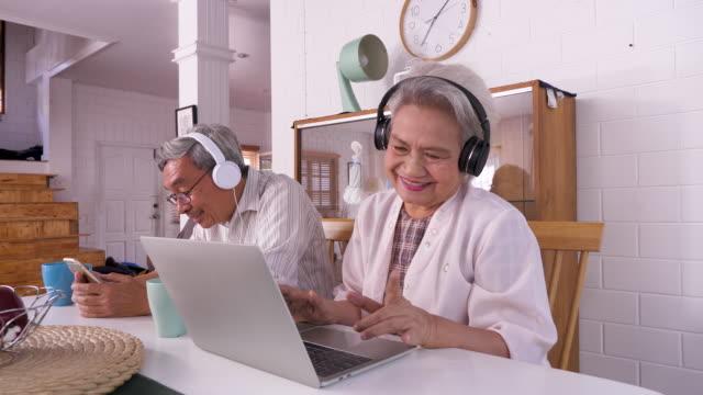 glücklichasiatische senior-paar mit laptop-computer und handy, während genießen musik zu hause zu hören, familie entspannen und verbringen zeit zusammen zu hause, ruhestand menschen und lifestyle-konzept - freundschaftliche verbundenheit stock-videos und b-roll-filmmaterial