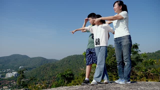 Happy Asian Single mother and her children enjoying together on mountain top view, adventure concept.