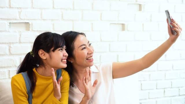 幸せなアジアの十代の娘と中年の母親は、自分撮りやビデオ通話を取ります - 母娘 笑顔 日本人点の映像素材/bロール