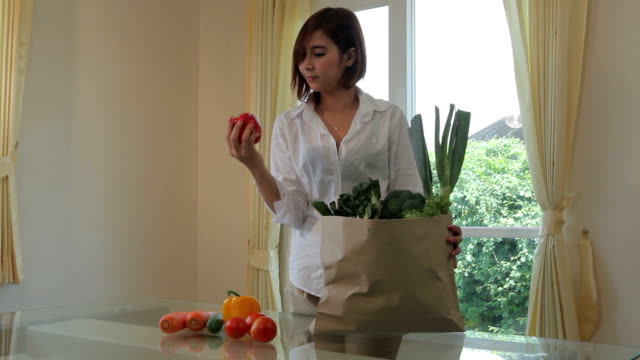 Happy asian woman cooking vegetables green salad in the kitchen video