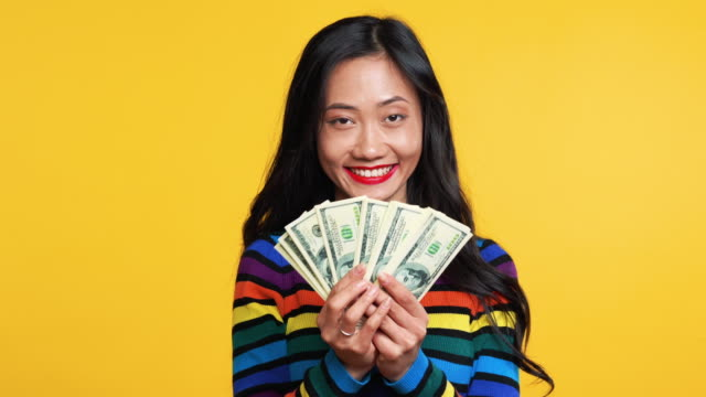 Happy asian woman holding stack of money