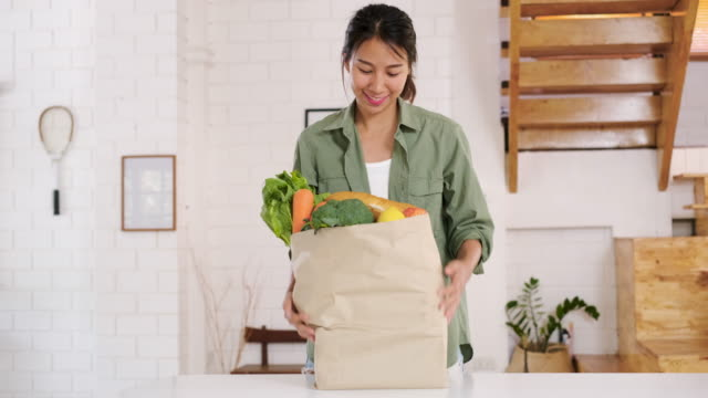 Happy asian woman  holding vegetable bag walking into kitchen after shopping at grocery store at home.vegan lifestyle concept video