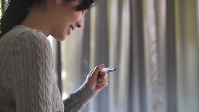 vídeos y material grabado en eventos de stock de mujer asiática feliz está embarazada usando prueba de embarazo - planificación familiar