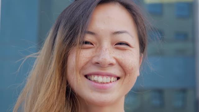 glad asiatisk kvinna tittar in i kameran och leende i staden - kinesiskt ursprung bildbanksvideor och videomaterial från bakom kulisserna