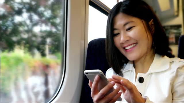 アジアの女性の幸せな列車の携帯電話を使用しています。 ビデオ